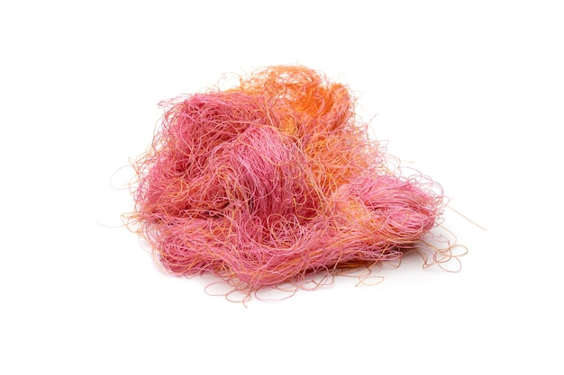 Pile of messy colorful yarn with selective focus on an isolated white background