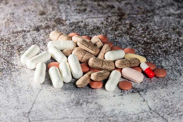 Pile of mixed pills and tablets in the foreground