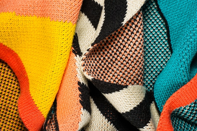 A pile of multi-colored synthetic knitted fabrics of different structures and textures.