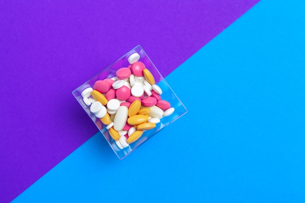 A pile of multicolored pills on blue background. top view.