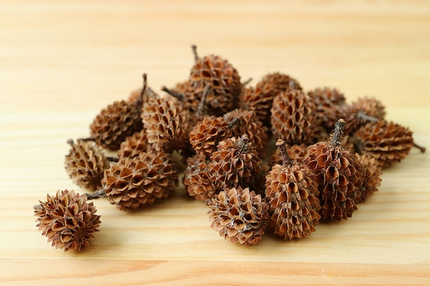 Pile of natural dry tiny pine cones on light brown wooden table