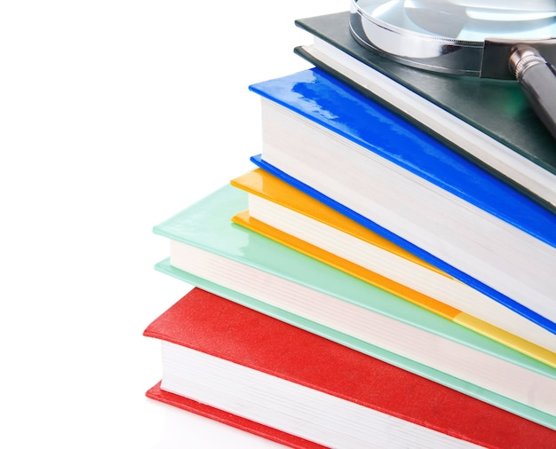Pile of new books and magnifying glass isolated on white