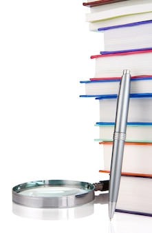 Pile of new books, pen and magnifying glass isolated on white wall