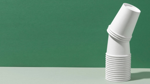 Pile of new cups copy space green background