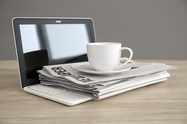Pile of newspapers, laptop and cup of coffee on wooden table