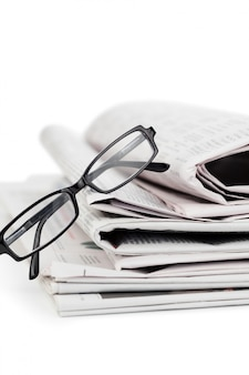 A pile of newspapers and a pair of reading glasses