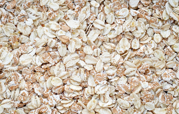 Pile of oat-flakes, background of uncooked oats. raw oatmeal.