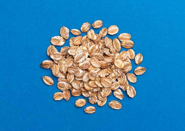 Pile of oat flakes on blue background top view