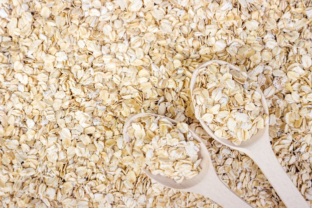 Pile of oat flakes and wooden spoon on oat flakes