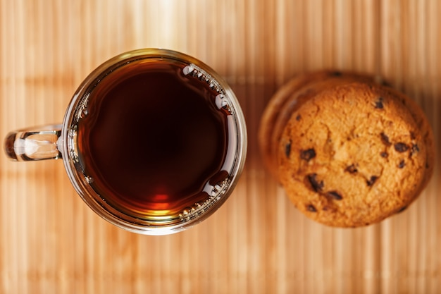 A pile of oatmeal cookies with chocolate chips and a mug of fragrant black hot tea