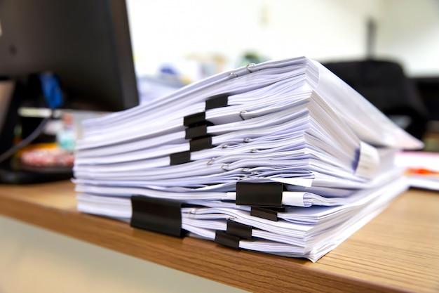 Куча много бумажных документов на стол офиса складывают.