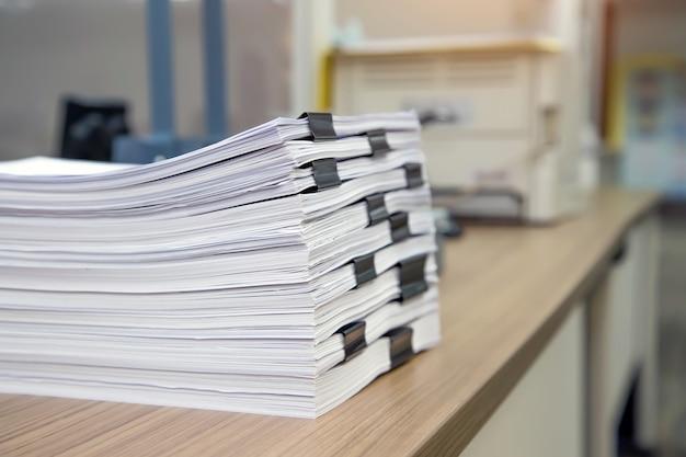 机のオフィスにたくさんの紙や書類のレポートの山。