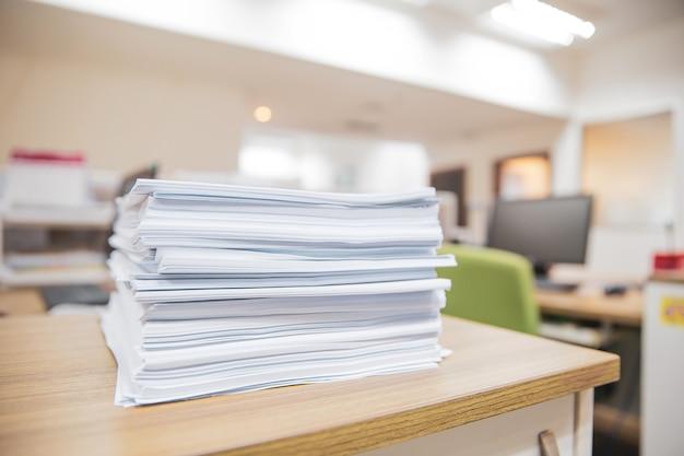 積み上げられたオフィスの机の上の紙の山。