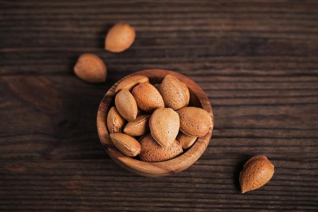 暗い木製の背景のボウルにアーモンドナッツの山。彼らの殻の新鮮なナッツ。