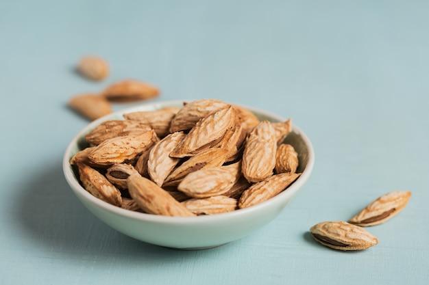 水色の背景のボウルにアーモンドナッツの山。彼らの殻の新鮮なナッツ。