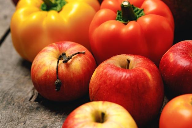 木製のテーブルにリンゴとピーマンの山