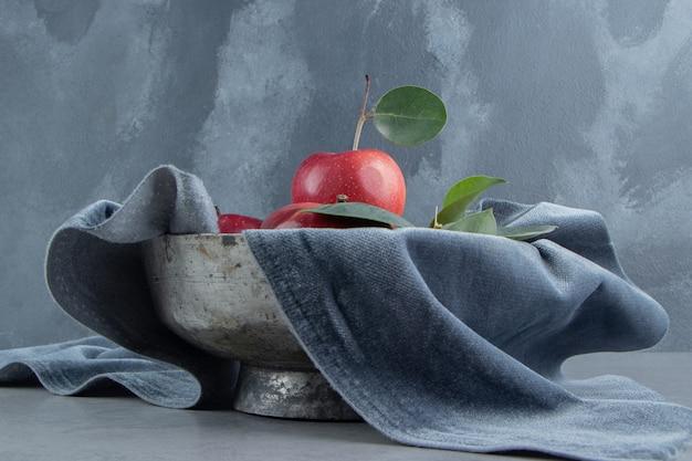 금속 그릇에 사과 더미 대리석 식탁보로 덮여있다.