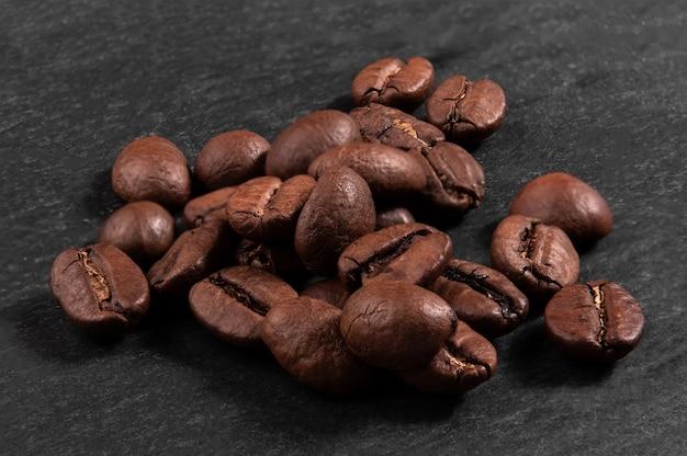 濃い黒の背景のクローズアップにアラビカコーヒー豆の山。マクロ撮影