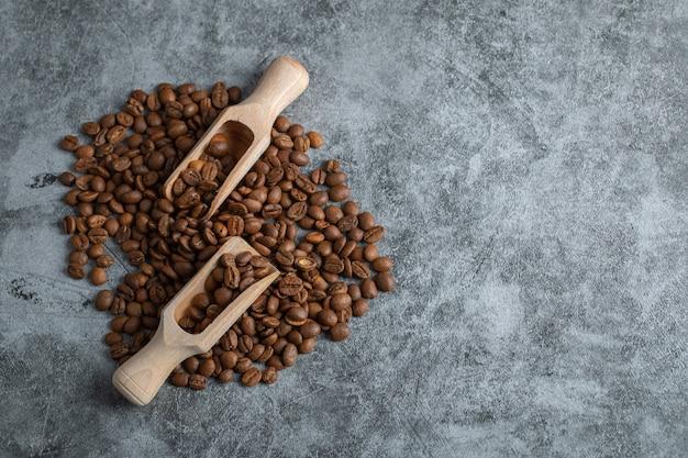 Куча ароматных кофейных зерен и деревянных ложек на мраморном фоне