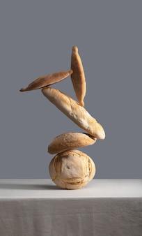 コピースペースのあるテーブルクロスで覆われたテーブルの上のバランスの取れたパンの山