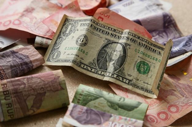 木製の表面にさまざまな国からの紙幣の山