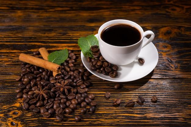 一杯のコーヒーと豆とスパイスの山