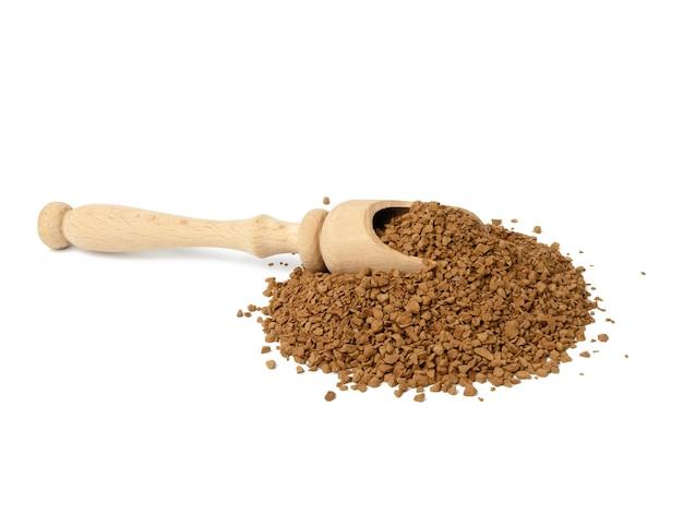 Куча гранул черного кофе и деревянной ложкой изолированы, крупным планом