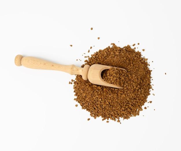 Куча гранул черного кофе на белой поверхности, вид сверху