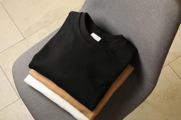 椅子の上の空白のスタイリッシュなスウェットシャツの山