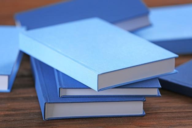 Куча синих книг на деревянном столе