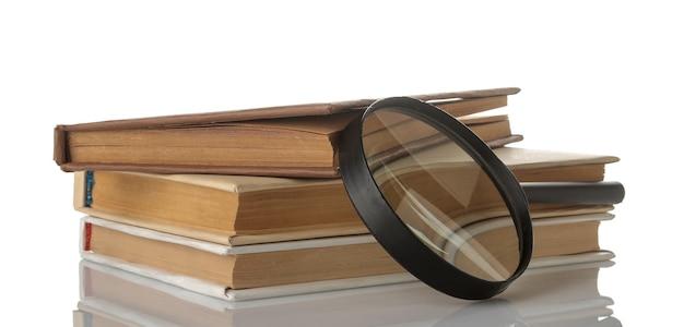 Куча книг и лупа на белом изолированном фоне. старые книги. образование. школа. учиться