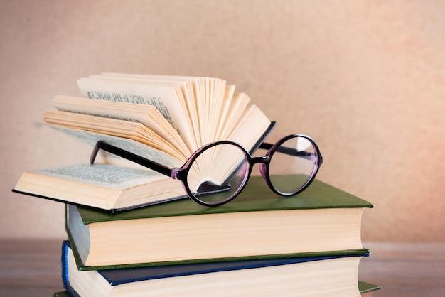 木製のテーブルの上に本と眼鏡の山、クローズアップ