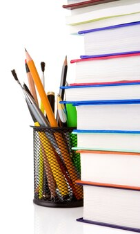 Куча книг и держатель корзины с ручками, изолированные на белой стене