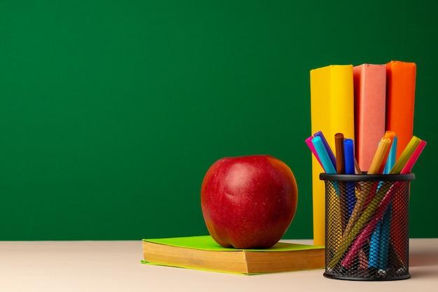 机の上の本と赤いリンゴの山