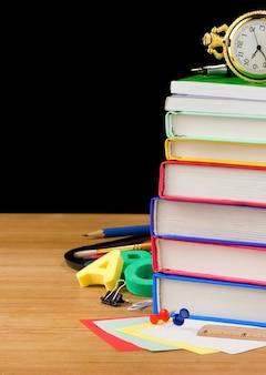 책과 학용품의 더미는 검은 배경 질감에 고립