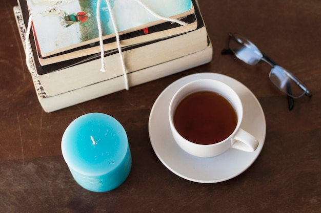 本、ろうそく、コーヒー、テーブル上の眼鏡の山