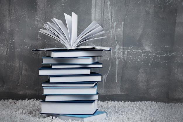 회색 벽에 카펫에 책 더미