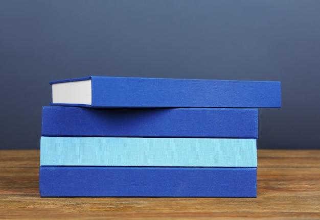 木製のテーブルと灰色の本の山