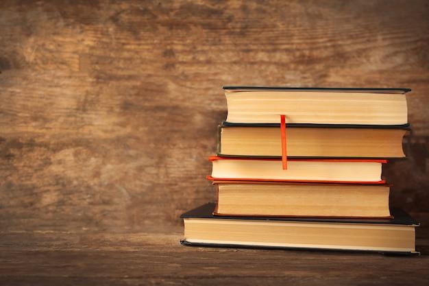 木製のテーブルの上の本の山