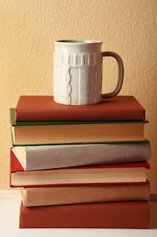 가벼운 벽에 탁상에 뜨거운 음료 한잔과 함께 책 더미
