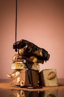 Куча сломанного шоколада на столе на коричневом фоне студии и брызги горячего шоколада