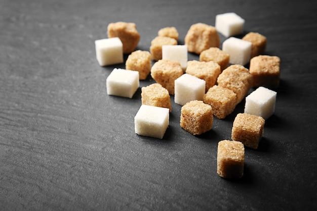 Куча коричневых и белых кубиков сахара на столе