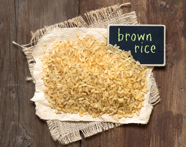 Куча коричневого риса с небольшой доске на вид сверху деревянный стол