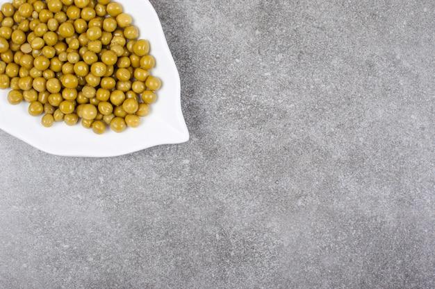 白いプレートに缶詰のエンドウ豆の山