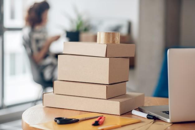 사무용품 중 노트북 앞에 둥근 나무 탁자 위에 쌓인 판지 상자 더미