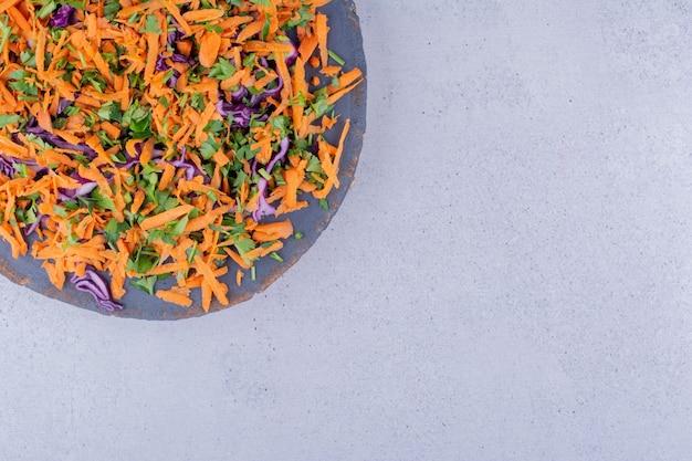 당근과 붉은 카바그테 더미는 대리석 배경의 보드에 샐러드로 잘게 썬다. 고품질 사진