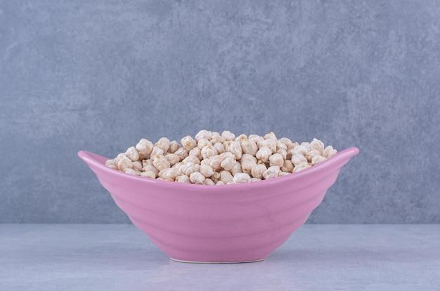 대리석 표면에 보라색 그릇에 가득 chickpeas의 더미