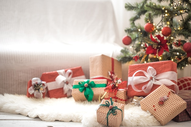 Куча рождественских подарков над светлой стеной на деревянном столе с уютным ковриком. рождественские украшения