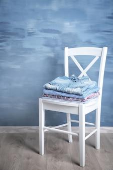 木製の椅子に服の山