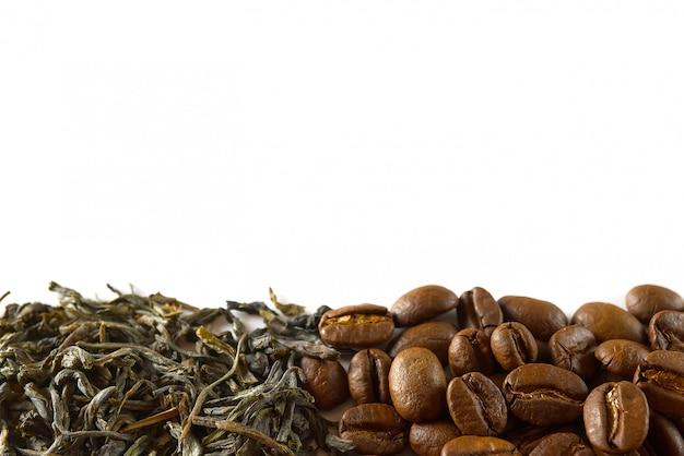 Куча кофейных зерен и сухих листьев зеленого чая изолированных на белой предпосылке.